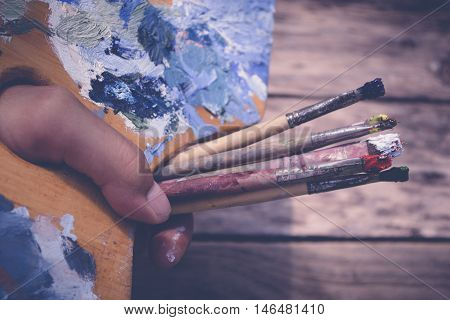 Old palette and brushes in multi-colored paint