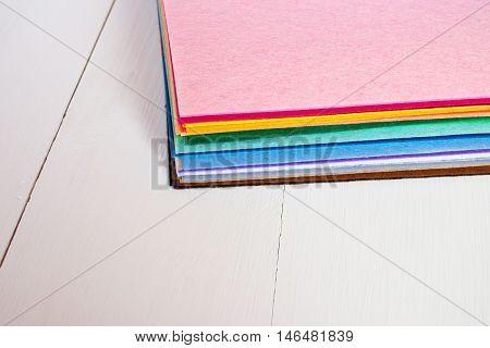 Colored felt sheets on wooden background. Colored felt set