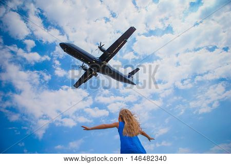 Little adorable girl looking at flying airplane