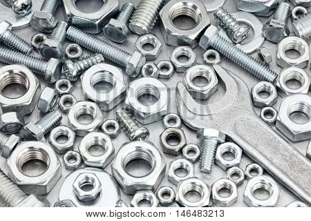 Various Bolts And Screws Of Different Size With Wrench On Scratched Metal Background