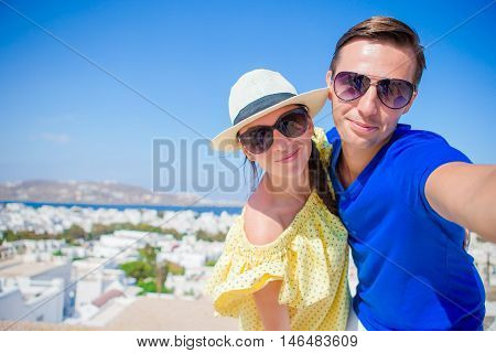 Selfie couple taking pictures at Mykonos island, Cyclades.