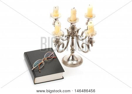 Candlestick book and glasses isolated on a white background.