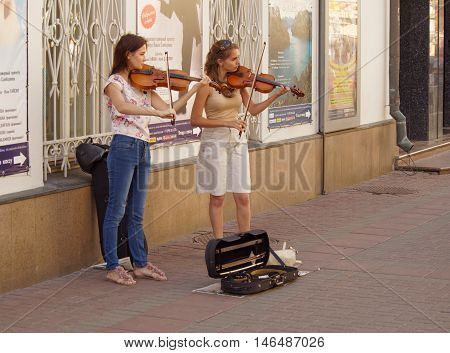 MOSCOW, RUSSIA - August 28, 2016: Two young women students playing violins on the sidewalk of Arbat street. August 28, 2016 in Moscow, Russia