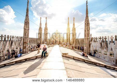 Milan, Italy - June 06, 2016: Tourists on the rooftop terrace of Duomo cathedral with beautiful decorated gothic spires. Duomo cathedral is the most famous sightseeing in Milan