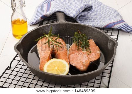 raw salmon steak with lemon thyme and rosemary in a cast iron pan