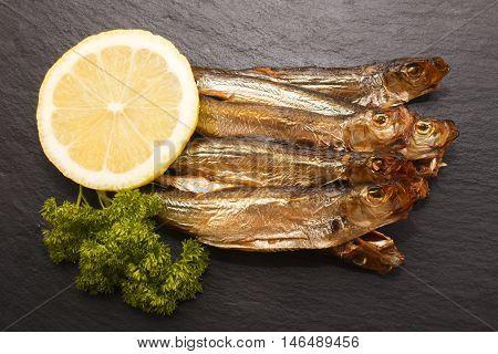 smoked sprats with slice lemon and parsley on slate