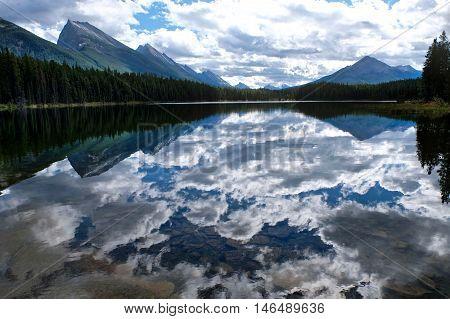 Clouds reflections in Honeymoon lake in Canadian Rockies. Jasper National Park. Alberta. Canada.
