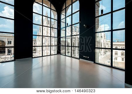 Milan, Italy - June 07, 2016: Big hall with windows in Novecento museum with great view on Duomo cathedral. Novecento is a museum of twentieth-century modern art in Milan, opened in December 2010