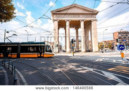 Milan, Italy - June 07, 2016: Street view on Ticinese city gate and tram in Milan. The gate of Porta Ticinese is one of the landmark buildings of Milan and a popular tourist attraction