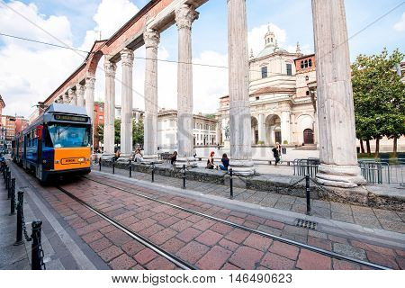 Milan, Italy - June 07, 2016: Street view with San Lorenzo Maggiore basilica, columns and old tram in Milan city.