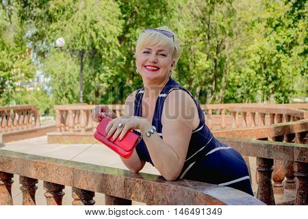 Happy woman in the park with a red handbag has leaned on a handrail
