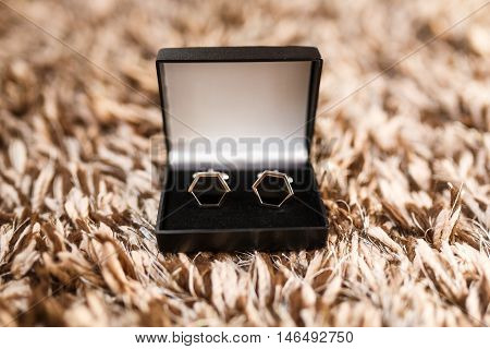 The cufflinks in a box on a wool surface