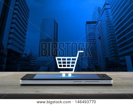 Shopping cart icon on modern smart phone screen on wooden table in front of city tower background Shop online concept