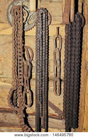 Old rusty chain hanging on the wall. Tool for bicycle.