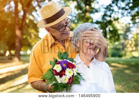 Senior Man Giving Bouquet Of Colored Flowers To His Wife