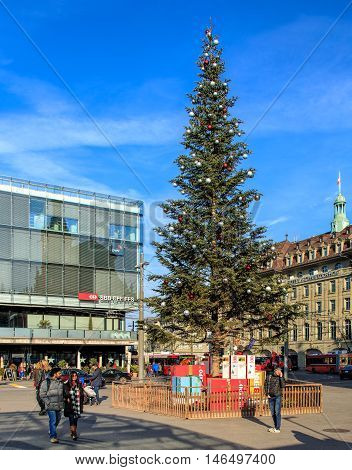 Bern, Switzerland - 29 December, 2015: pedestrians and a Christmas tree on Bahnhofplatz square, train station and Hotel Schweizerhof buildings in the background. The city of Bern is the capital of Switzerland.