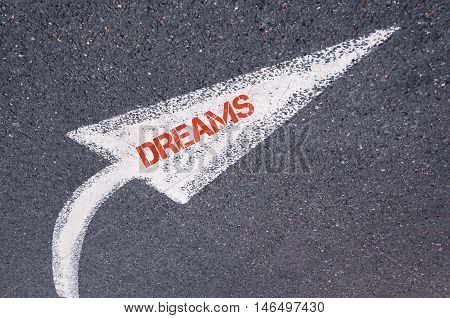 Directional White Painted Arrow With Word Dreams Over Road Surface