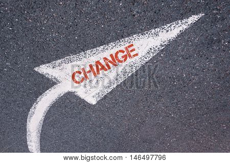 Directional White Painted Arrow With Word Change Over Road Surface
