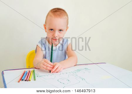 Little boy at a desk learning to draw with markers and pencils. Child with a felt-tip pen. Photo with limited depth of field.