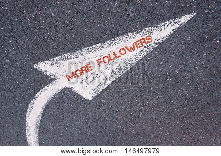 Directional White Painted Arrow With Words More Followers Over Road Surface