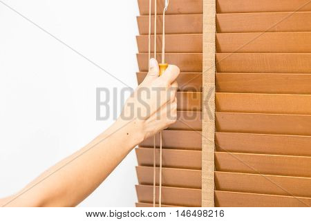 Hand pull closed wood blinds closed at windows.