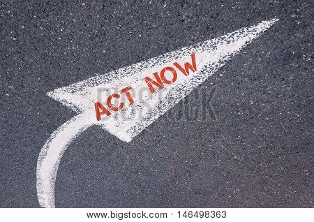 Directional White Painted Arrow With Words Act Now Over Road Surface