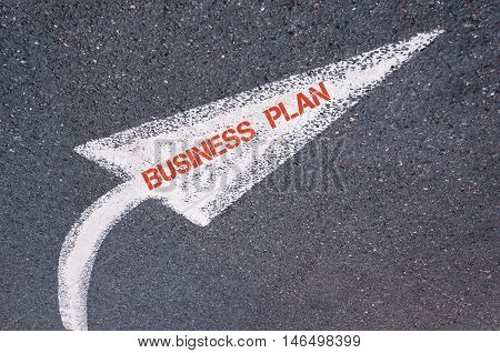 Directional White Painted Arrow With Words Business Plan Over Road Surface