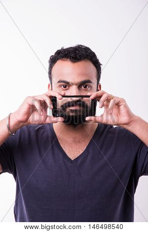 indian bearded man showing picture of beard in smartphone, young indian man with beard showing beard pic on mobile