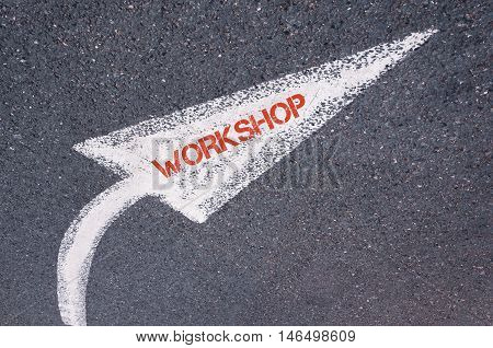 Directional White Painted Arrow With Word Workshop Over Road Surface
