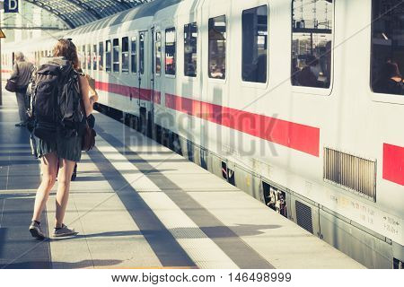 Girl with backpack from behind standing at plattform before entering train.