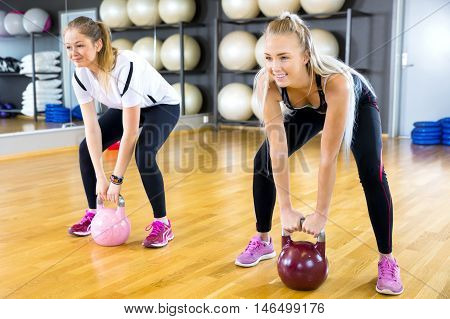 Group workout at a fitness center. Kettlebell weight workout at the gym.