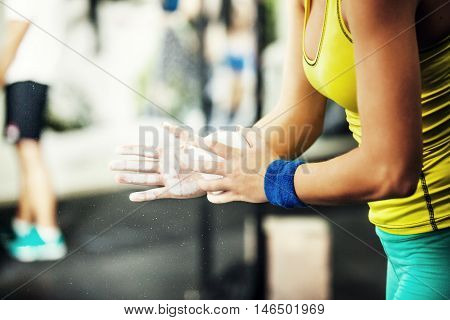 Young fit woman is preparing hands with talc for cross fit training.