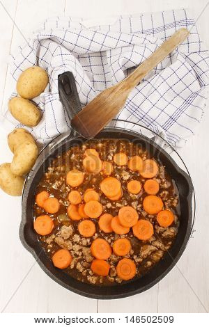 mince with onion carrot and gravy in a cast iron pan