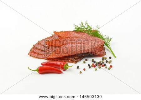 Thin slices of black pepper salami with peppercorns and red chili peppers