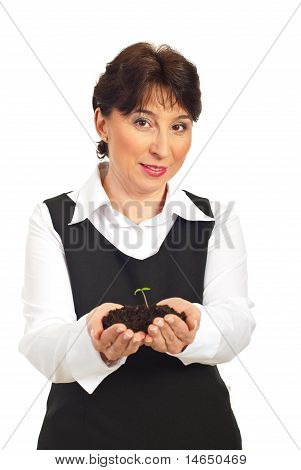 Smiling Mature Woman Holding Plant