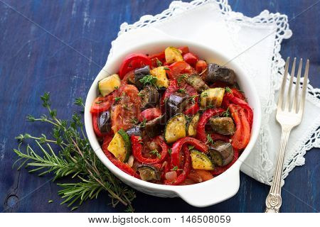 Ratatouille a traditional French dish of vegetables in a white ceramic bowl on a dark blue background, selective focus