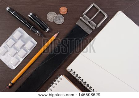 Flat Lay Top View Business Concept. Accessory Belt With Pen, Notebook And Chewing Gum On Wooden Tabl