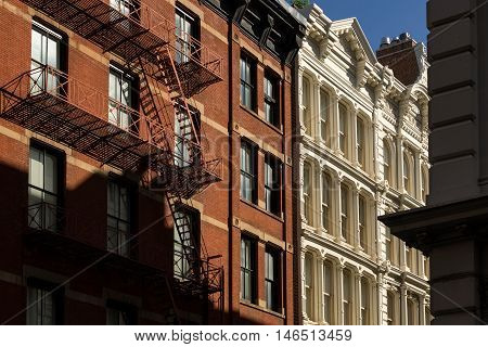 Soho buildings with brick and cast iron facades and fire escape. Manhattan, New York City