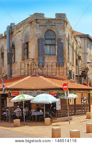 TEL AVIV, ISRAEL - August 24, 2016: tourists rest in small cafe on one of the streets in the Old City of Jaffa on august 24, 2016 Tel Aviv, Israel