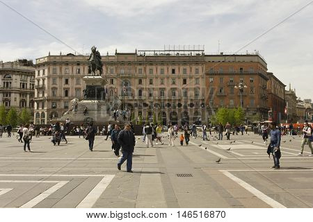 MILAN, ITALY - APRIL 14 2015: Piazza del Duomo square in Milan monument to King Victor Emmanuel II and the Palazzo Carminati behind it and people around