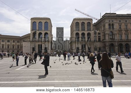 MILAN, ITALY - APRIL 14 2015: View of Piazza Diaz Skyscraper and Museo del 900 from Piazza del Duomo in Milan Italy with people around
