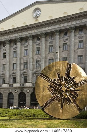 MILAN, ITALY - APRIL 14 2015: Banca Popolare di Milano headquarter with a bronze sculpture by Arnaldo Pomodoro in the foreground