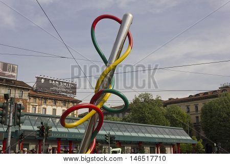 MILAN, ITALY - APRIL 16 2015: The giant sculpture of a needle and threat in Piazza Cadorna in Milan with the Ferrovie Nord train station in the background