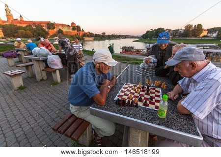 KRAKOW, POLAND - FEB 8, 2016: Unidentified elderly mens play chess on the embankment of Vistula. There are about 40 parks in Krakow including dozens of gardens and forests.