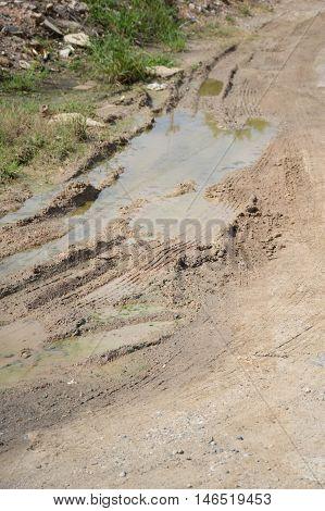 close up wheel tracks on wet soil in garden