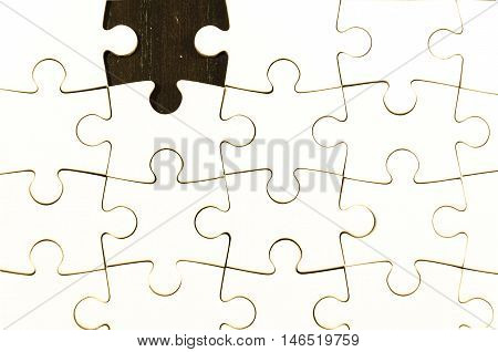 white jigsaw/puzzle whit one gap over black wooden table background symbol of problem solving
