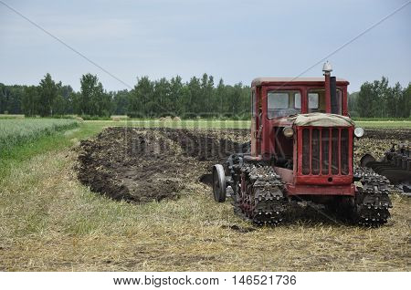 Tractor on the agricultural field cultivating soil to a forest background.
