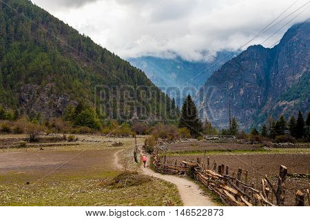 Nepalese Sherpa Hiking Mountain Trail Village.Old Man Walking Loaded Bags Track Traveler Beautiful Noth Asia.Himalaya Summer Valley Landscape Background.Horizontal Photo