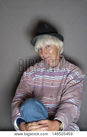 Female with gray hair and wearing men hat posing in studio with a sneering look on her face.