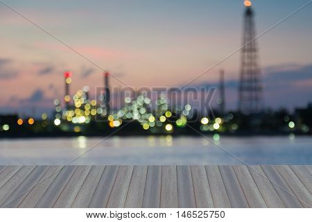 Opening wooden floor, blurred lights water front over oil refinery